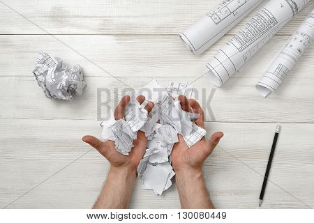 Masculine hands palm up with pieces of paper. Despair. Top view composition. Anger sign. Worry process. Workplace of architect or constructor. Engineering work. Construction and architecture. Architect drawing. Draft.