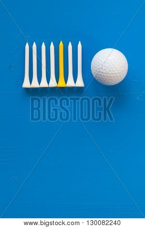 Golf ball and wooden golf tees on the wooden blue desk