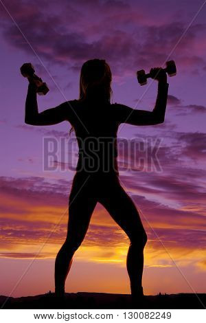 A silhouette of a woman in the outdoors working out with dumbbells.