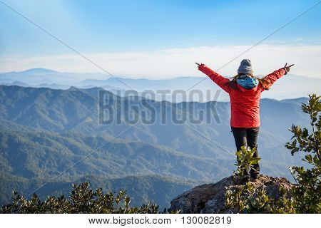 Woman traveler in red coat climb on the rock and upraised arms on top of mountain among beautiful spring landscape - can use for joy or travel concept
