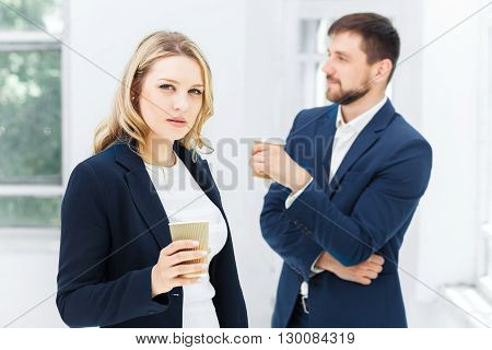 Young colleagues having coffee break, chatting in office
