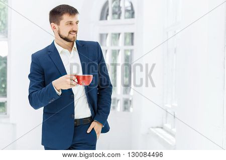 Businessman having a coffee break, he is holding a red cup