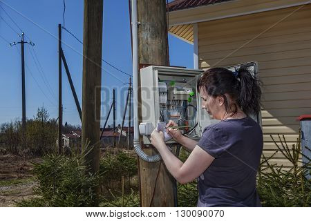 Peasant Woman looking electric meter data in switchgear mounted on a wooden pole near farm house in countryside.