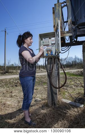 Woman checking electric meter reading standing near electricity switchgear power transformer substation outdoors.
