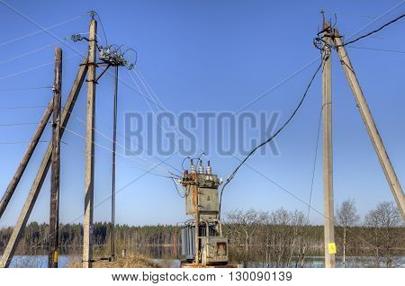 Electricity supply power lines from local electrical substation connected to a distribution transformer in the countryside springtime.