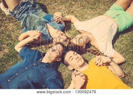 Friends lying and relaxing on the grass . They are two girls and two boys resting at park holding hands and keeping eyes closed. Beautiful image of friendship and togetherness.