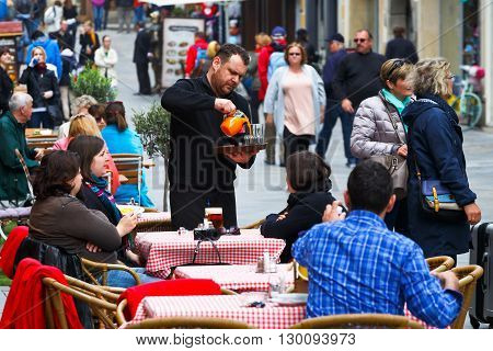 BRATISLAVA, SLOVAKIA - MAY 16, 2016: Waiter serving customers in a coffee shop in the old town of Bratislava, Slovakia on May 16, 2016.