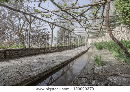 Old stone orangery with water channel and a vineyard.