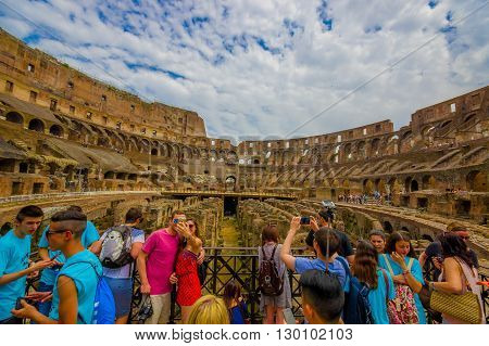 ROME, ITALY - JUNE 13, 2015: Turists enjoying inside Roman Coliseum, people taking photographs and visiting this World heritage monument.