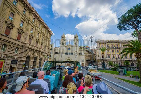 ROME, ITALY - JUNE 13, 2015: Turists bus visiting the most important places in Rome city, people watching from their seats. Church in the center of Rome