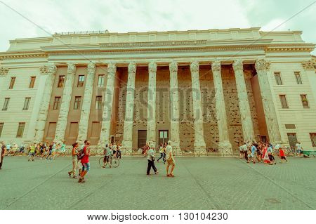ROME, ITALY - JUNE 13, 2015: Nice structure in the center of Rome, building with various columns and windows, turists crossing.