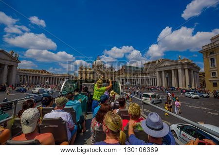 VATICAN, ITALY - JUNE 13, 2015: Turists bus visiting the most important places in Rome city, people watching from their seats. Saint Peter Basilica