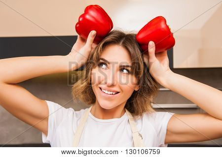Funny picture of a woman holding big papricas above her head