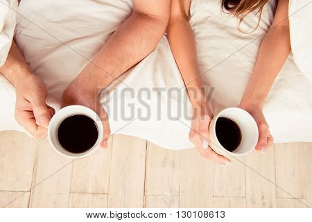 Close up photo of hands of two lovers holding cups with coffee