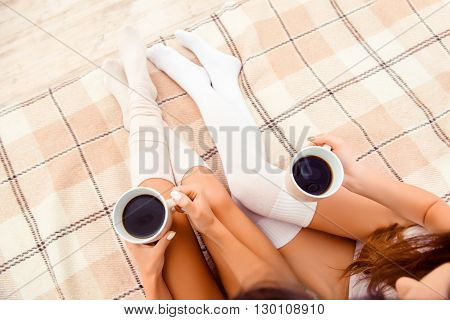 Top View Of Beautiful Women's Legs In White Stockings With Cups Of Coffee