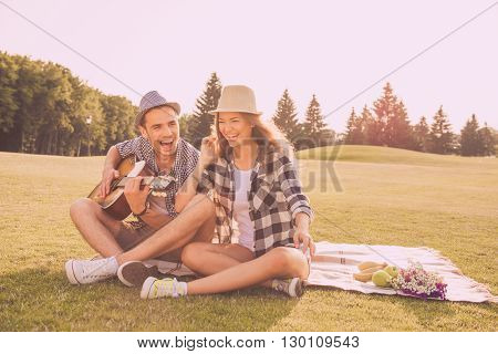Happy Couple In Love Having Picnic In Park With Guitar