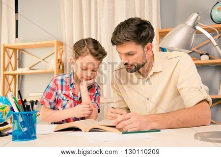 Father And Son Siting With Interesting Book And Studing