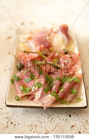Deli or lunch meat and some greens in a rectangular plate