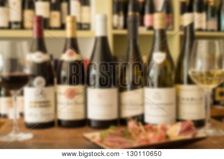 A row of bottles of wine and a deli plate between wineglasses on wooden surface and a wine collection in the background