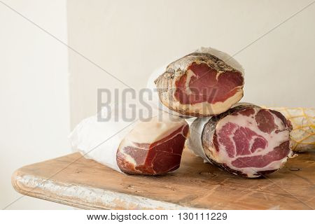 Logs of cured or preserved meat on a wooden counter