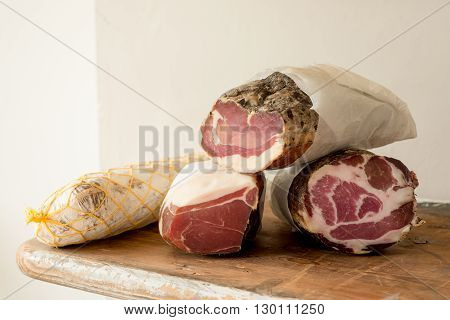 Logs of deli meat on a wooden counter
