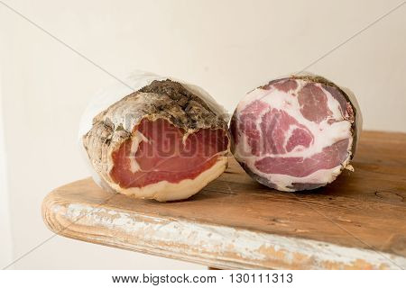 A couple of deli meat logs on a wooden counter
