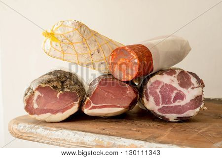 Logs of ham or lunch meat on a wooden counter