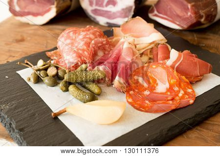 A variety of sliced lunch meat alongside fruits and pickled cucumbers on a stone block with deli meat logs in the background