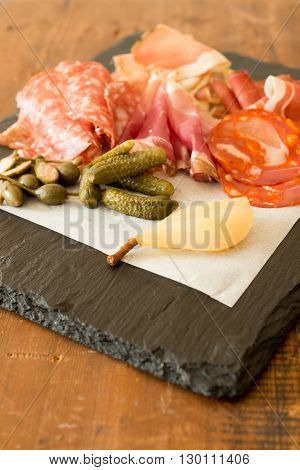 Various sliced cold cuts or deli meat with pickles and fruit on a stone block