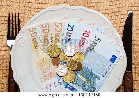 Cost of living price of food and eating wealth concept. Euro money on kitchen table plate with cutlery