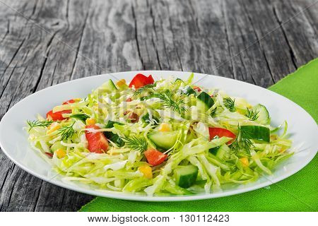 Healthy low calories spring cabbage salad with bell pepper corn cucumber and dill on a white dish simply and easy recipe studio lights close-up top view