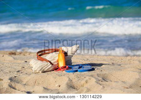 bag, suncream, flip flops on the beach, vacation concept