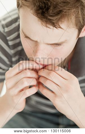 Overhead View Of Nervous Boy Chewing Nails