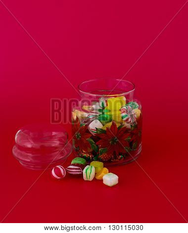 Jar with colored candies isolated on red background- stock photo