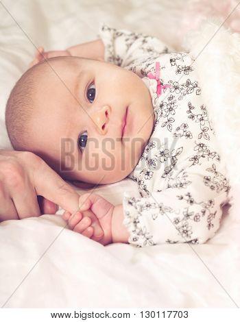 Newborn baby girl grasping her parents finger poster