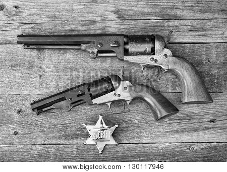 The guns that won the west and sheriff badge in black and white.