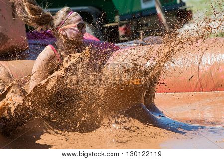 HAMPTON, GA - APRIL 2016:  A woman creates a large splash of muddy water as she lands in a mud pit at the Dirty Girl Mud Run obstacle course event in Hampton GA on April 23 2016 .