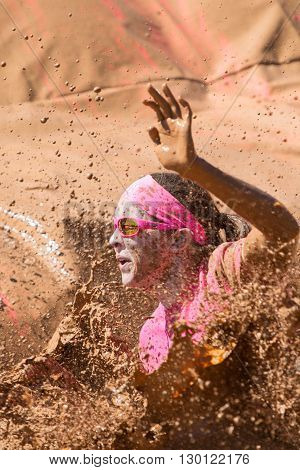 HAMPTON, GA - APRIL 2016:  A woman splashes muddy water as she lands in a mud pit at the Dirty Girl Mud Run obstacle course event in Hampton GA on April 23 2016 .