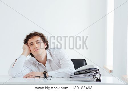 Tired businessman sitting at the table with papers and looking at camera