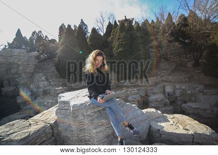 Beautiful girl sitting in the park with a laptop and is bathed in sunshine