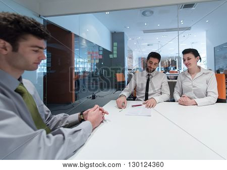 signing contract on partners back, young couple on business meeting with life insurance and bank loan agent at modern office interior
