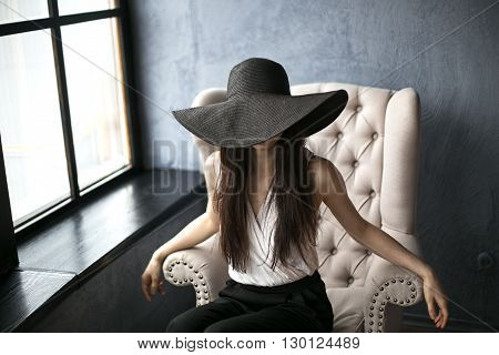 Young beautiful girl in the big black hat. Girl sits elegantly in a white chair. The girl's face is covered.