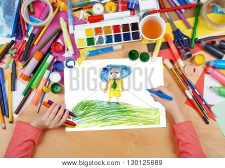 boy with blue hat on top meadow hill child drawing, top view hands with pencil painting picture on paper, artwork workplace