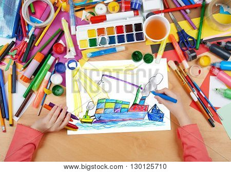 dry cargo ship with containers, transportation concept, child drawing, top view hands with pencil painting picture on paper, artwork workplace