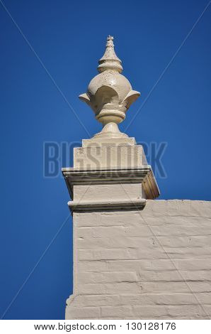 A globe-shaped finial on the top wall of a rendered-brick building.