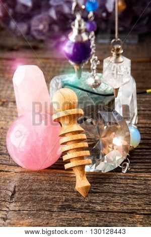 Pendulums.Wooden, crystal pendulum, amethyst, tool for dowsing. Crystals undrneath and in backbround.