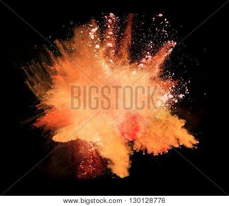 Explosion of orange powder on black background