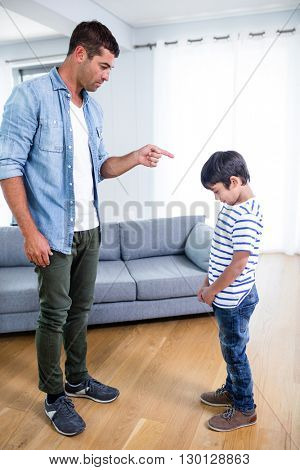 Angry father scolding his son in living room at home