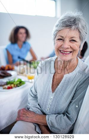 Portrait of senior woman sitting at dinning table and family in background