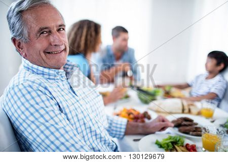 Portrait of senior man sitting at dinning table and family in background